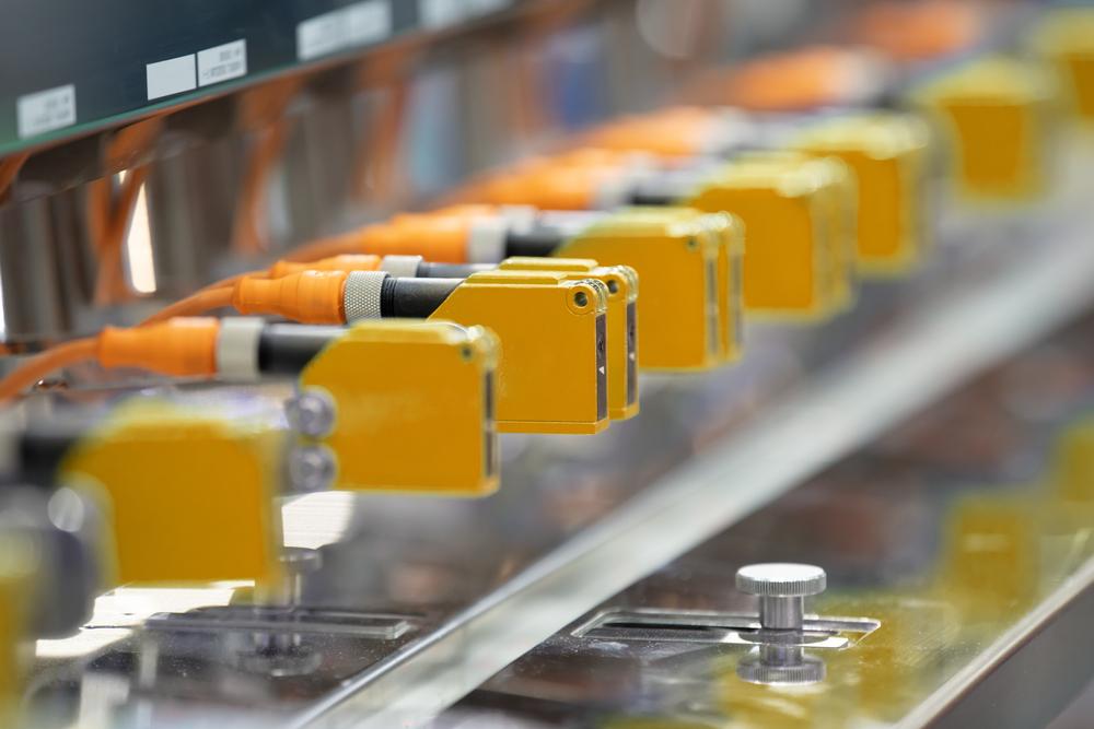 Capteur photoelectrique installe dans une rangee de machines industrielles dans une usine. Capteur photo pour la detection dobjets en usine de machines.