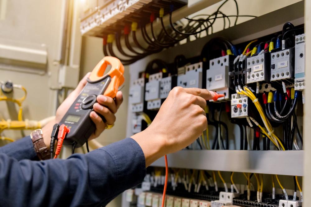 Essai de travail de lelectricien ingenieur mesurant la tension et le courant de la ligne electrique electrique dans le controle de larmoire electrique