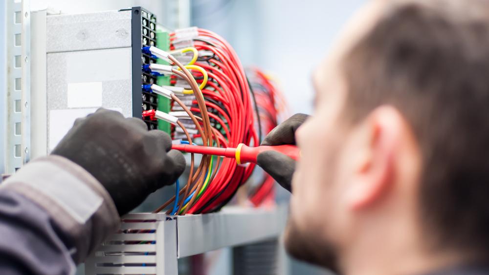 Gros plan sur un ingenieur electricien travaille avec des cables electriques de la boite de commutation de fusible. Equipement electrique